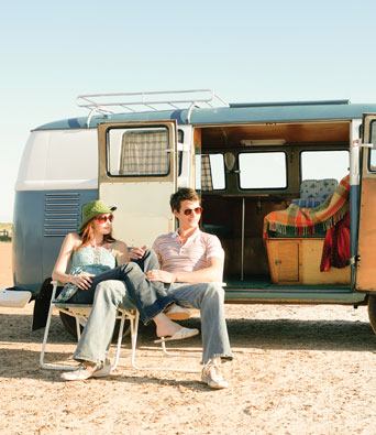 Couple sitting outside camper van resting from their travels