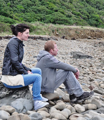 Couple sitting on a rocky beach looking out to sea