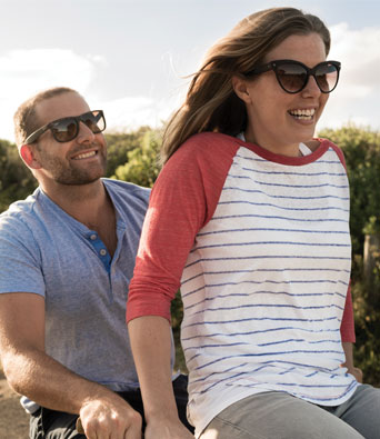 Man in blue shirt riding bike with girl in stripy top on the handlebars