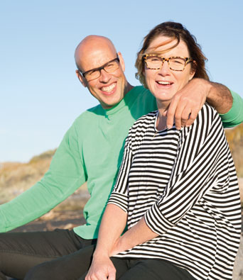 Green shirt and striped couple sitting on beach