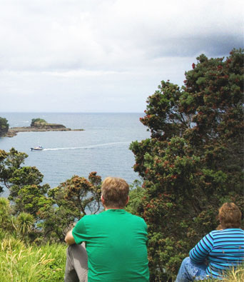Couple sitting at top of grassy hill looking out to a harbour
