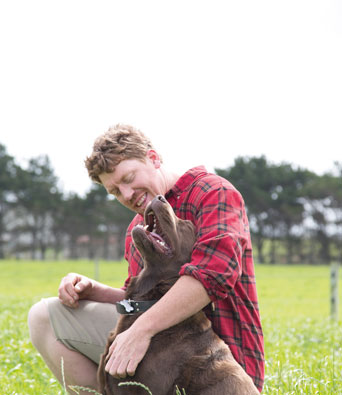 Farmer in red checked shirt in field hugging brown dog