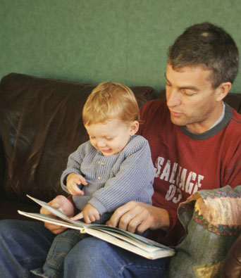 Father and young son reading a book together on the sofa