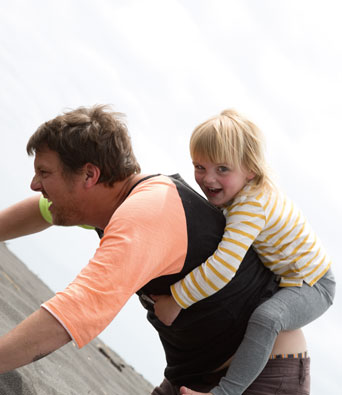 Father giving young child in yellow and white top a piggyback