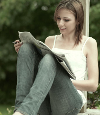 Young brunette woman sitting down in jeans and white top reading the newspaper