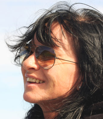 Lady wearing sunglasses smiling with wind blowing hair across her forehead
