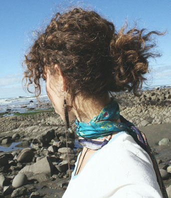 Curly haired lady on rocky beach