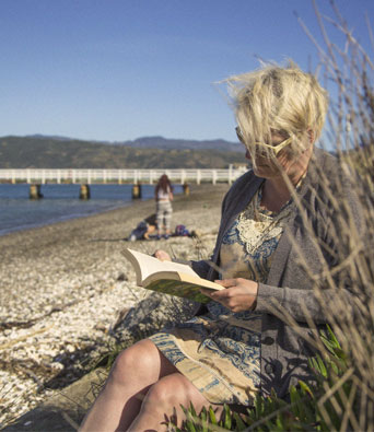 Retired lady with blonde hair reading on the beach in a grey cardigan
