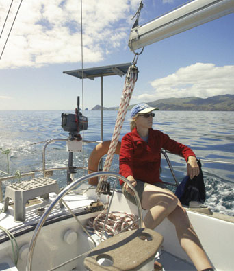 Lady in red fleece and cap sailing yacht in Hauraki Gulf