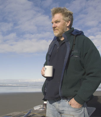 Man in green fleece standing on beach drinking coffee from mug