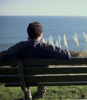 Man sitting on bench on cliff overlooking ocean