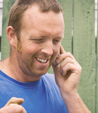 Man in blue t-shirt smiling on phone