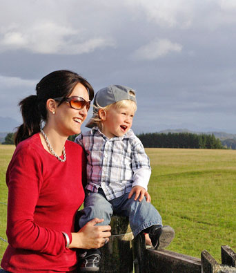 Mother in red top holding son sitting on wooden fence by field