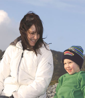 Mum in white jacket sitting with young son on beach