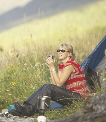 Woman in red stripy top camping beside river
