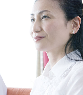 Woman in white shirt with long dark hair listening to financial advice