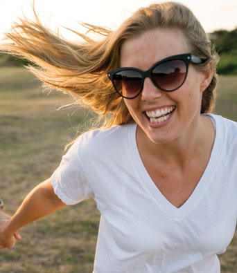 Woman with long hair laughing as she runs through a field