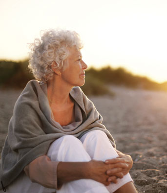 Grey haired woman in white trousers sitting on a beach at sunset