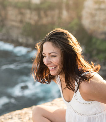 Young woman laughing on clifftop