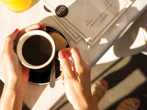 Aerial view of female hands around a coffee cup on desk