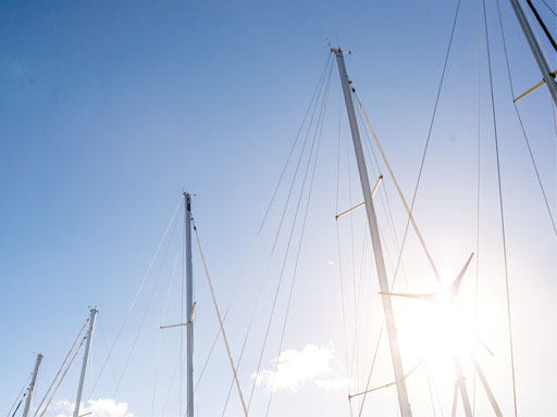 Masts of boats against a blue sky with sun shining through stays