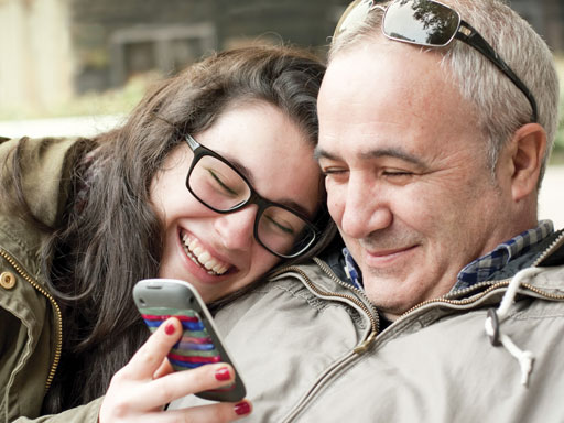 Father and daughter laughing over mobile phone images