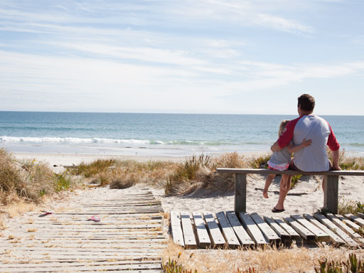 Father and daughter sitting on a bench looking out to sea with arms around each other