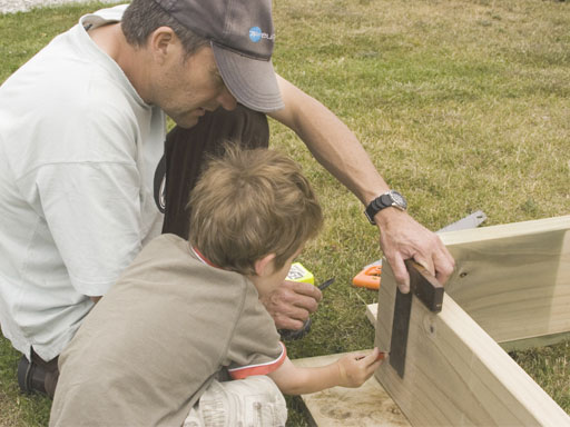 Father and son building frame to sandpit