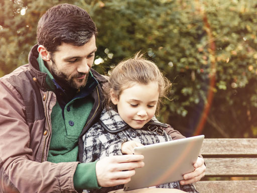 Father sitting with daughter on bench looking for help on ipad