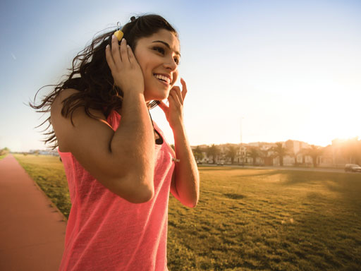 Girl with long brown hair jogging through park with headphones