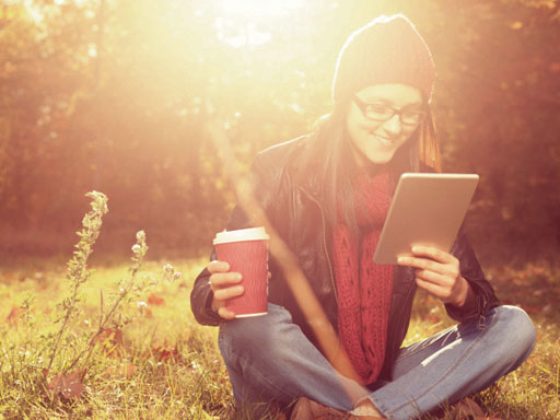 Girl sitting crossed legged on the grass with take-away coffee and ipad in hands