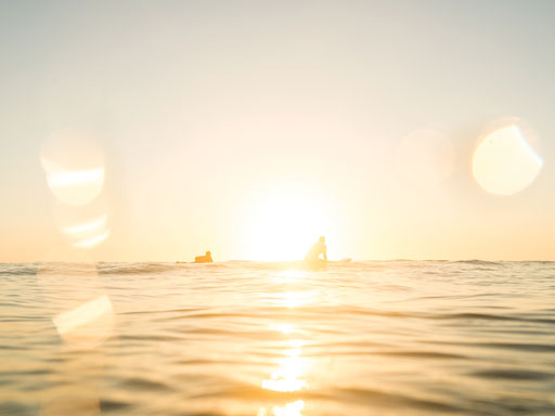 Golden sun bouncing off water with two surfers in the water waiting for a wave
