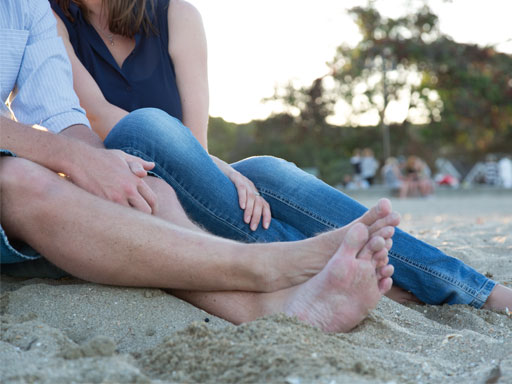 Couple sitting on beach with a close up of their legs
