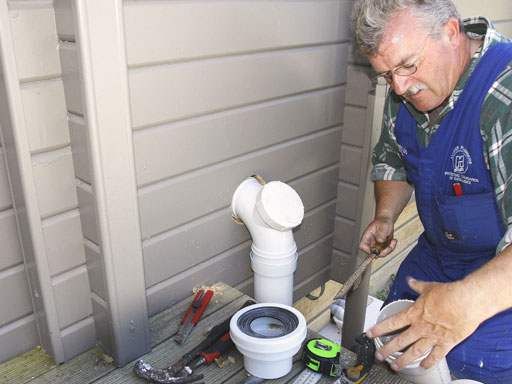 Man working outside on house pipes