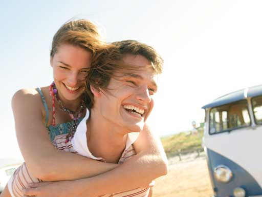 Young couple laughing outside blue and white camper van