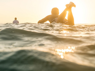 Surfers on water at sunset